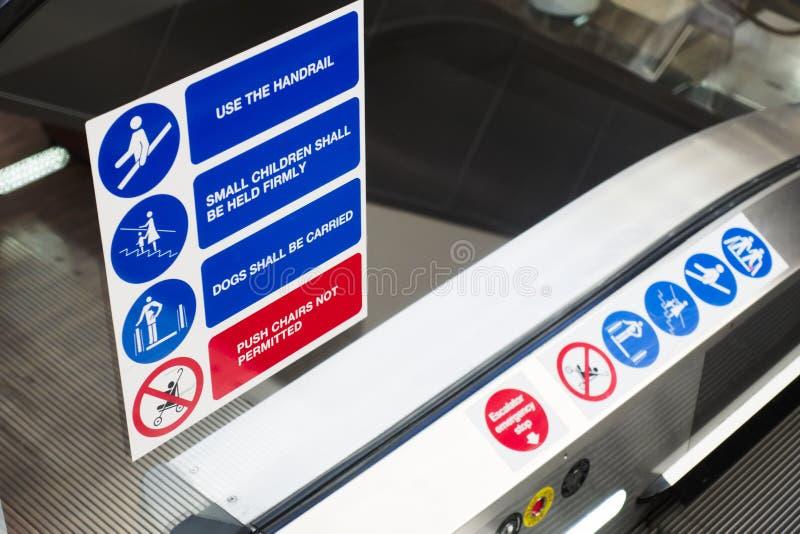 De het tekensymbolen van de roltrapveiligheid sluiten omhoog en tekst op glas boven elektrische lift stock foto