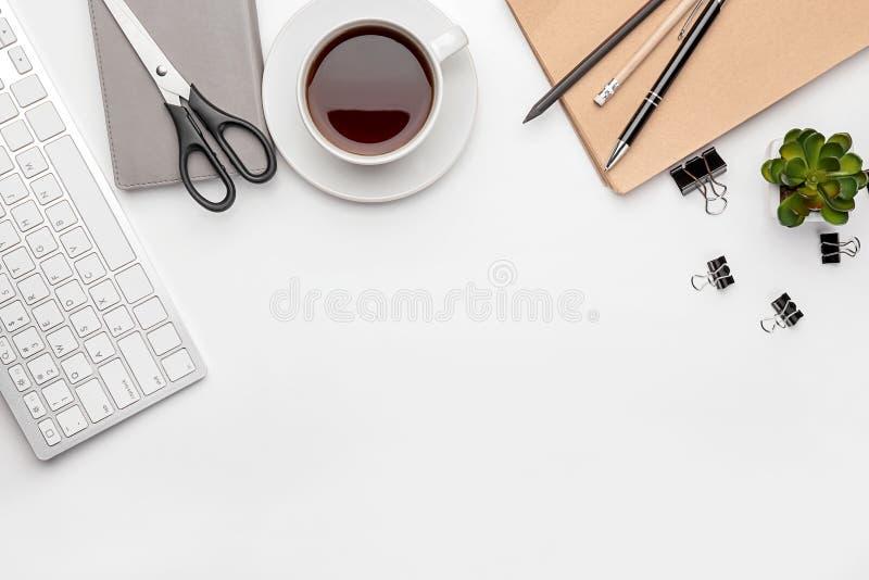 De het vlakke computertoetsenbord, kop van koffie en de kantoorbehoeften op witte achtergrond, leggen De samenstelling van de wer stock foto's