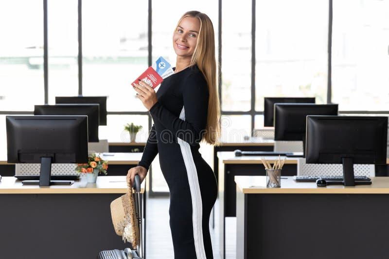 De het vrolijke paspoort en bagage van de bedrijfsvrouwenholding in werkplaats van bureau Het concept van de zomervakanties royalty-vrije stock foto's