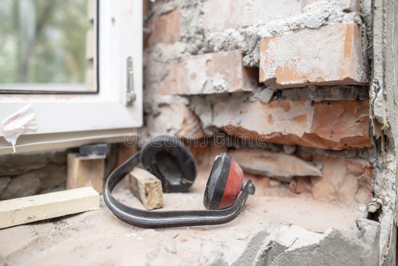De het werkhoofdtelefoons beschermen tegen lawaai die op een bakstenen muur dichtbij het pvc-venster liggen o stock foto's