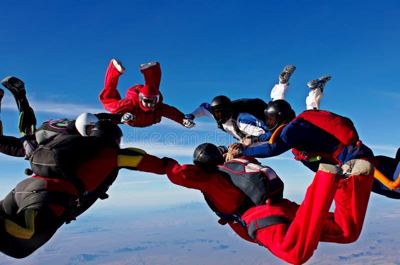 De het werkvorming van het Skydivingsteam maakt een cirkel stock fotografie