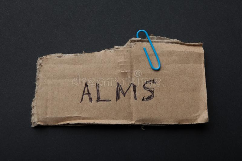 De het woord 'aalmoes op een stuk van karton op een zwarte achtergrond royalty-vrije stock afbeelding
