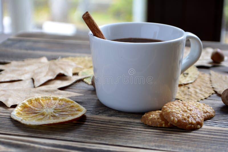 De hete chocolade met pijpje kaneel in kop verlaat notenkoekjes droge sinaasappelen op houten lijst royalty-vrije stock foto