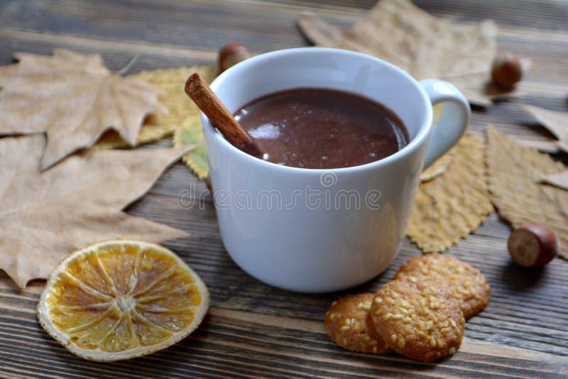 De hete chocolade met pijpje kaneel in kop verlaat notenkoekjes droge sinaasappelen op houten lijst royalty-vrije stock afbeeldingen