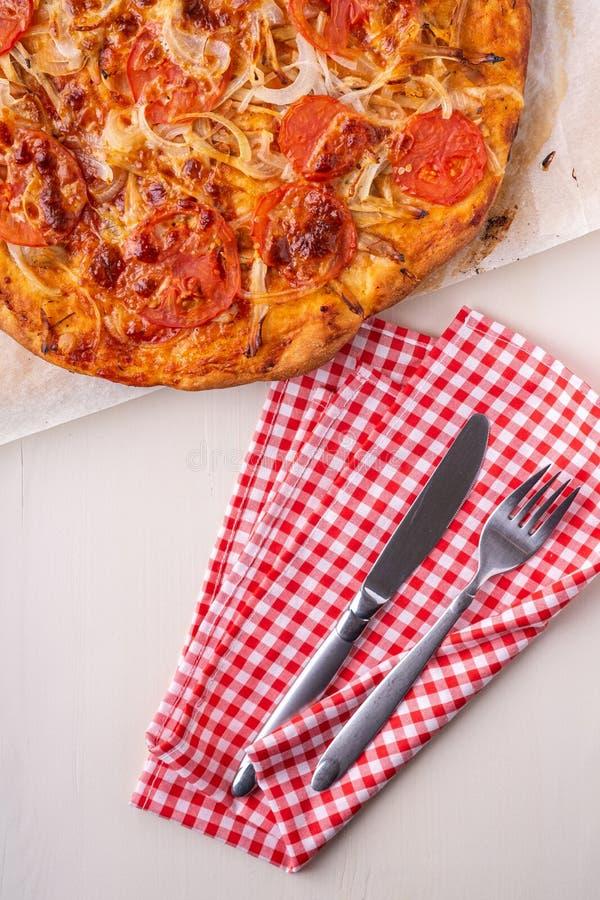 De hete eigengemaakte pizza met kippenvlees, tomaten, uien dichtbij met bestekvork en mes op rood vlak tafelkleed, legt, hoogste  stock foto