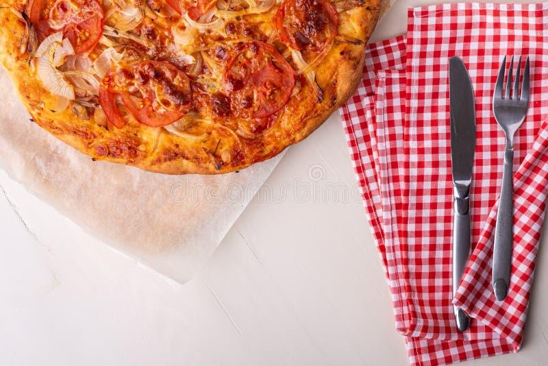 De hete eigengemaakte pizza met kippenvlees, tomaten, uien dichtbij met bestekvork en mes op rood vlak tafelkleed, legt, hoogste  stock foto's