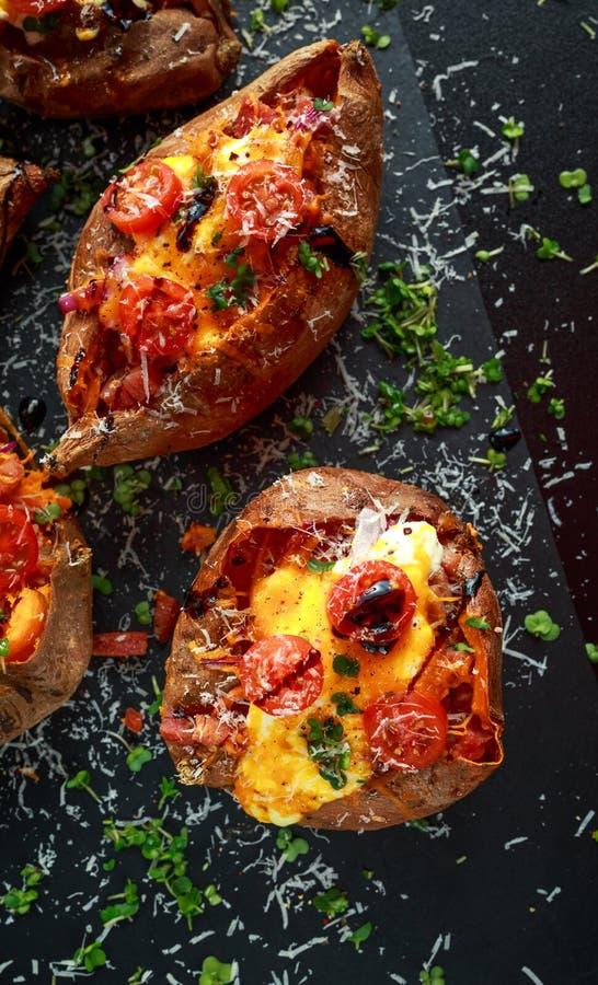 De hete gebakken bataat vulde met bacon, cheddarkaas, kersentomaten, balsemieke azijn, tuinkerssalade en parmezaanse kaas royalty-vrije stock fotografie