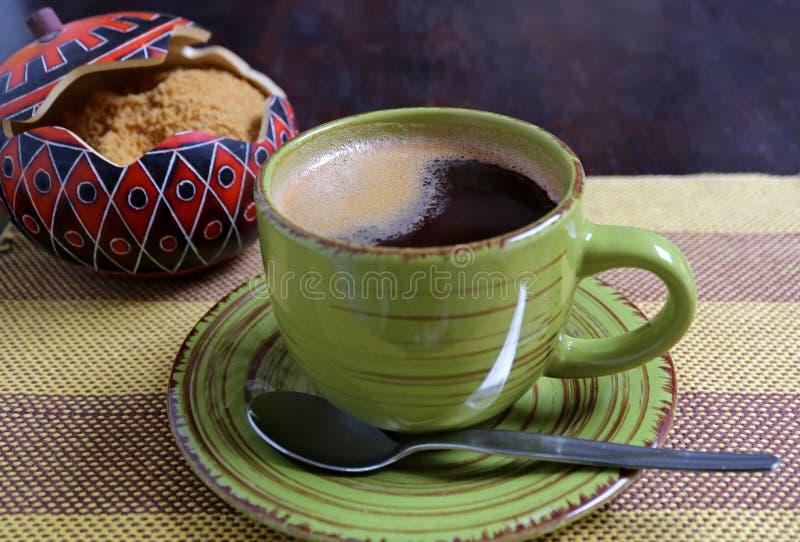 De hete koffie in een groene kop met vage suikerpot van bruine suiker in achtergrond diende op streeptafelkleed royalty-vrije stock afbeelding