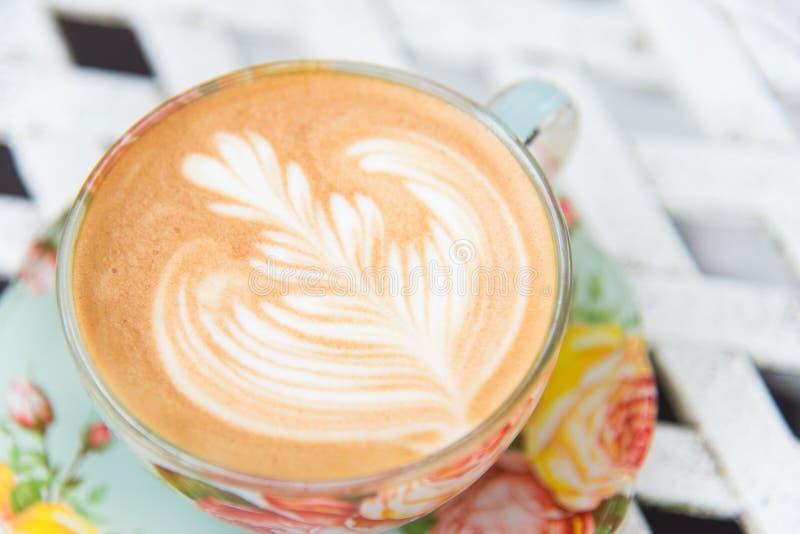 De hete koffie van de lattekunst op de uitstekende stijl dient de lattekunst in wordt gecreeerd in het mooie bladerencijfer in ui stock fotografie
