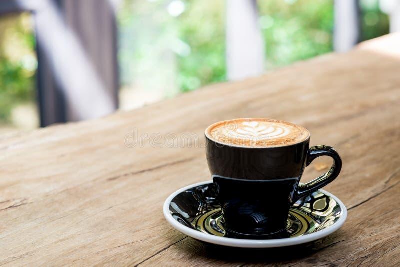 De hete kop van de cappuccinokoffie met het schuim van de de kunstmelk van de boomvorm latte op houten lijst dichtbij venster in  stock fotografie