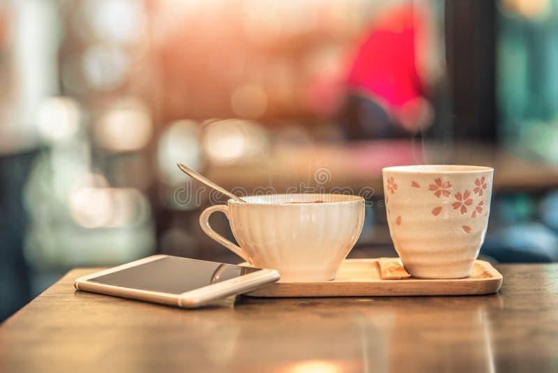 De hete kop van het koffieglas met smartphone op houten lijst in koffiewinkel Uitstekende toon royalty-vrije stock foto
