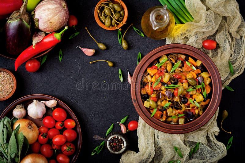De hete kruidige aubergine van hutspotcaponata, courgette, paprika, tomaat, wortel, ui, olijven en kappertjes royalty-vrije stock afbeeldingen