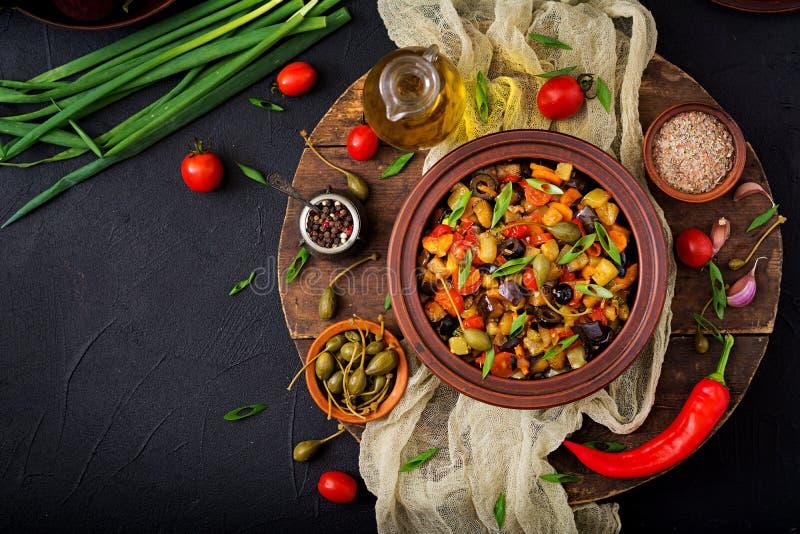 De hete kruidige aubergine van hutspotcaponata, courgette, paprika, tomaat, wortel, ui, olijven en kappertjes stock afbeelding