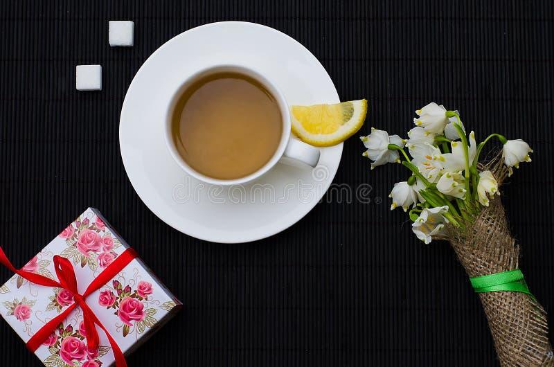 De hete thee van het de lenteontbijt en een boeket van sneeuwklokjes stock afbeeldingen