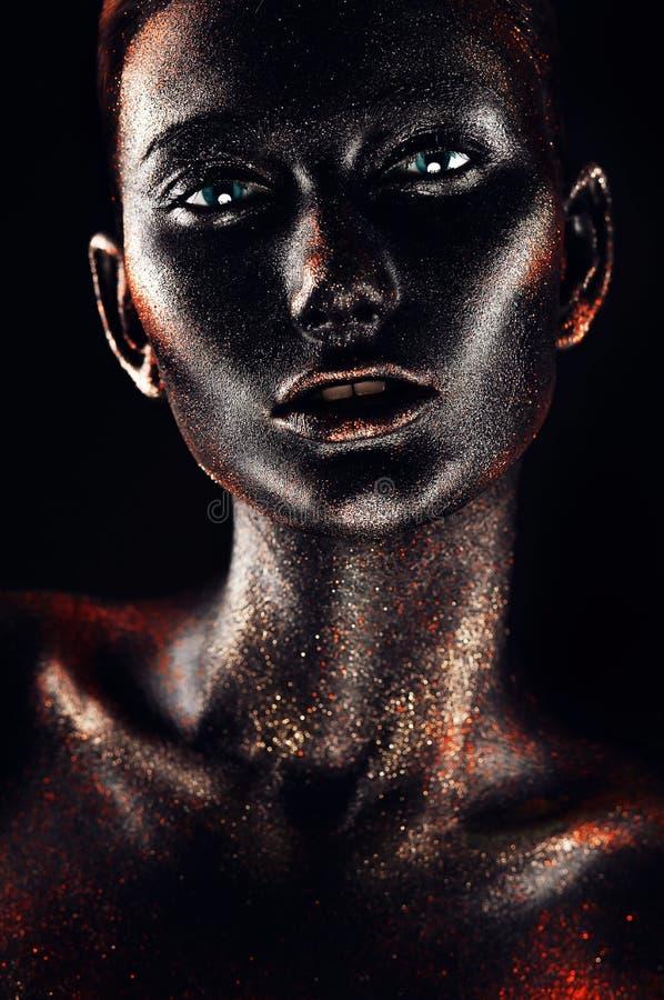 De hete vrouw in rood schittert en zwarte verf stock afbeeldingen