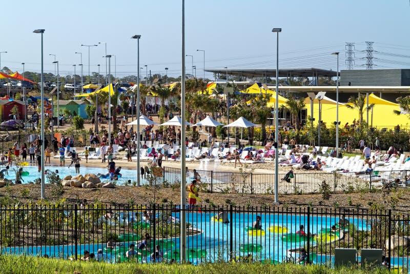 De hete de zomerdag met mensen in waterpark ontspant in en bij pool royalty-vrije stock afbeelding