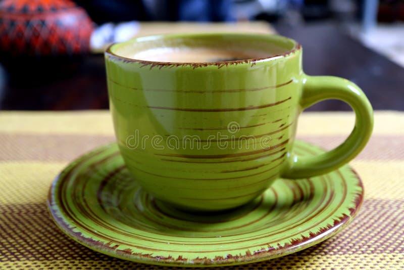 De hete zwarte koffie in een groene kop diende op streeptafelkleed, selectieve nadruk royalty-vrije stock fotografie