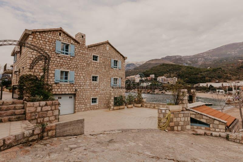 De heuvelige straat met uiterst kleine tuinen, die de plattelandshuisjes en de hotels, Budva Montenegro omringen royalty-vrije stock afbeeldingen