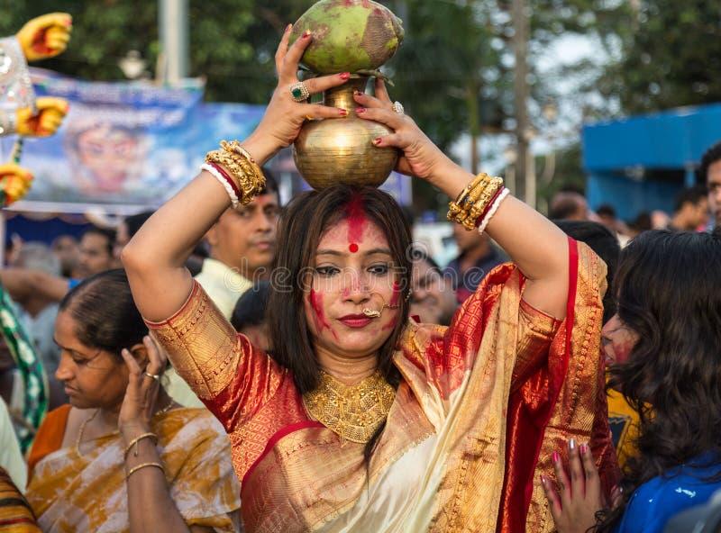 De Hindoese gehuwde vrouw houdt een waterkruik op haar hoofd als deel van een ritueel van Durga Puja-onderdompelingsceremonie stock afbeeldingen