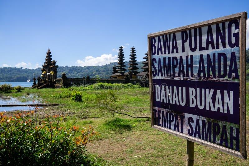 De Hindoese tempelruïnes van Pura Hulun Danu schepen voorzichtig teken in een rommel maken niet van bij het Tamblingan-meer, Bali stock fotografie
