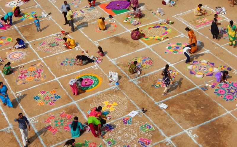 De Hindoese vrouw trekt rangoli met gekleurd poeder, bloemen in festiva van pongal of makarasankranti royalty-vrije stock foto's