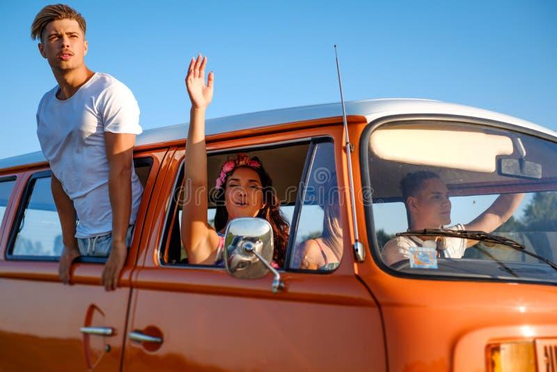 De hippievrienden in een bestelwagen op een weg halen over stock foto's