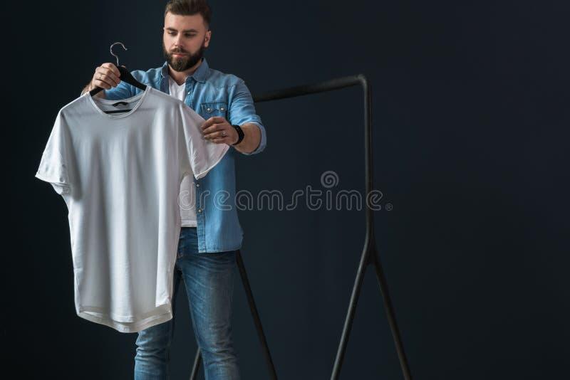 De Hipstermens kleedde zich in denimoverhemd en jeans, tribunes binnen en bekijkt witte T-shirt op kleerhanger in zijn handen stock foto