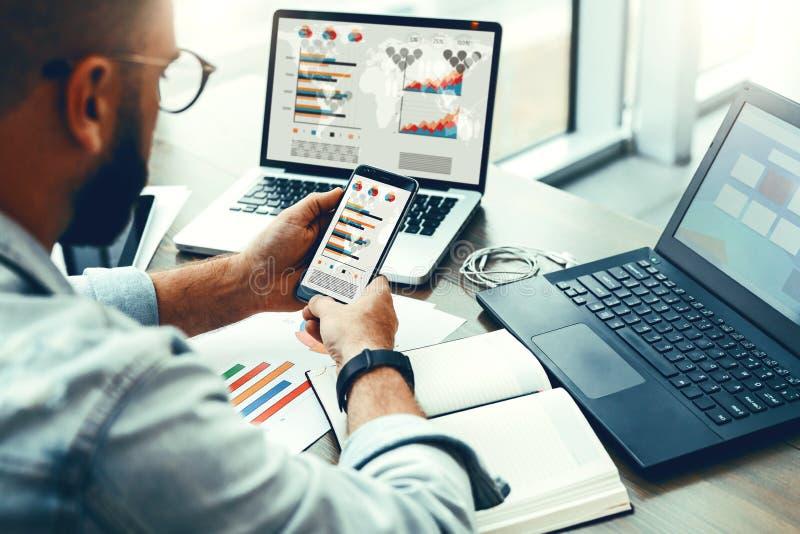 De Hipstermens zit in koffie, gebruikt smartphone, werkt aan twee laptops met grafieken, grafieken, diagrammen op het scherm Onli stock foto
