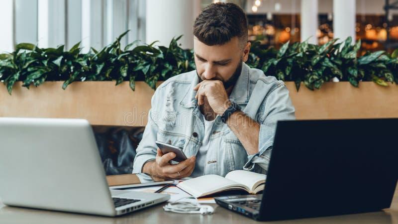 De Hipstermens zit in koffie, gebruikt smartphone, werkt aan twee laptops De peinzende zakenman leest een informatiebericht in te stock afbeeldingen