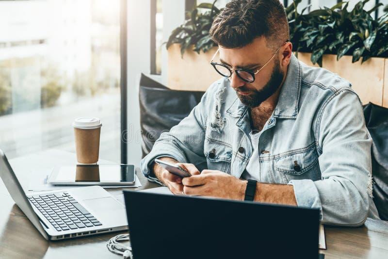 De Hipstermens zit in koffie, gebruikt smartphone, werkt aan twee laptops De zakenman leest een informatiebericht in telefoon royalty-vrije stock afbeeldingen