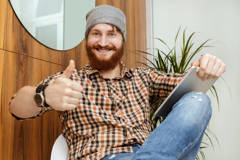 De Hipsterzitting op de stoel en het geven beduimelen omhoog royalty-vrije stock foto