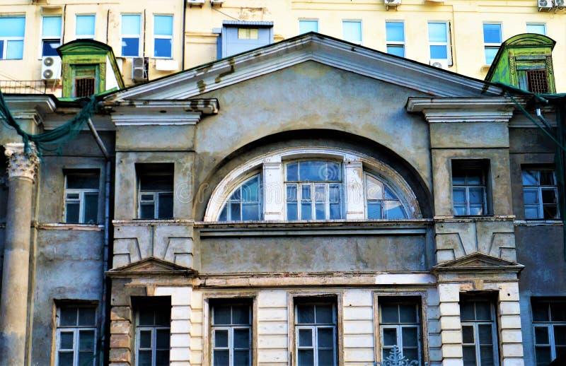 De historische bouw met grijze overspannen vensters tegen de achtergrond van een modern gebouw Selectieve nadruk stock afbeeldingen