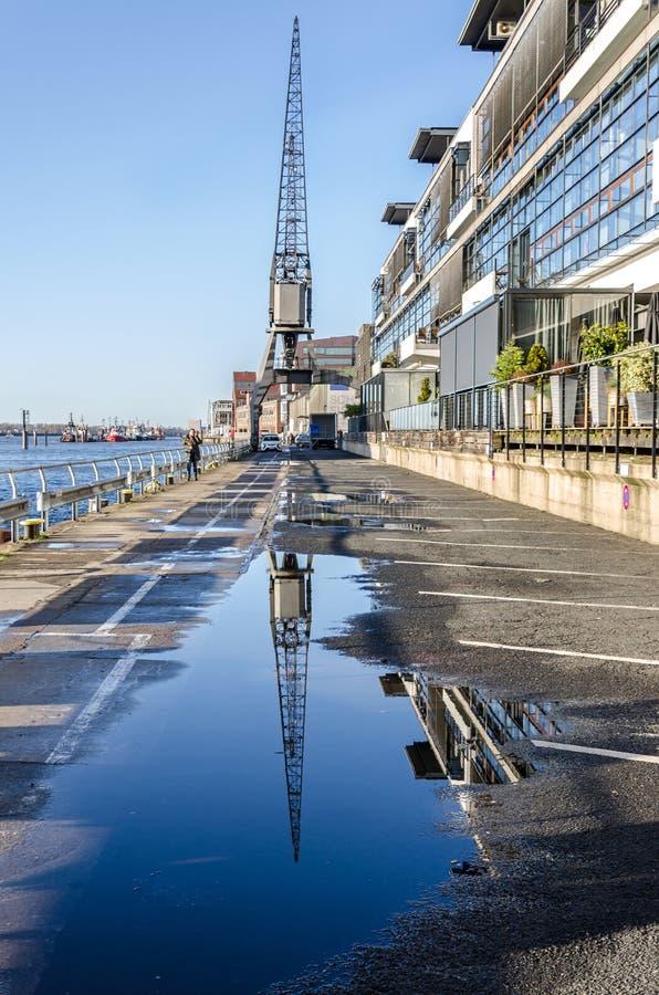 De historische havenkraan wordt weerspiegeld in een vulklei op de waterkant op Elbe rivier in Hamburg stock fotografie
