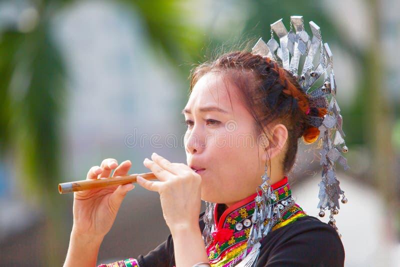 De Hmong kvinnorna på deras traditionella klänningar spelar deras eget musikinstrument