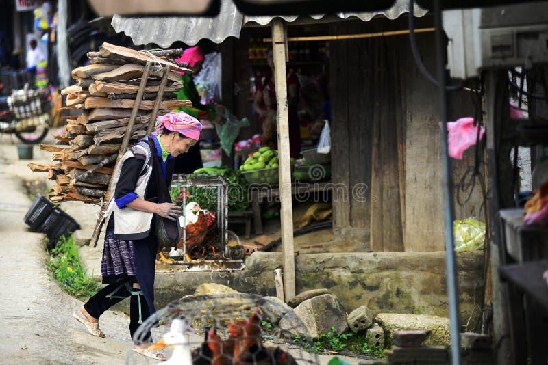 De Hmongvrouwen dragen firewook en lopend in het platteland van de ochtendmarkt van Vietnam royalty-vrije stock afbeelding