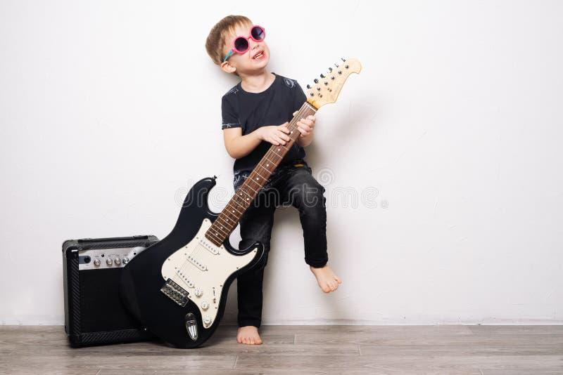 De hobbys van kinderen: een kleine jongen in zwarte glazen speelt de elektrische gitaar, imiteert een rotsster royalty-vrije stock afbeeldingen