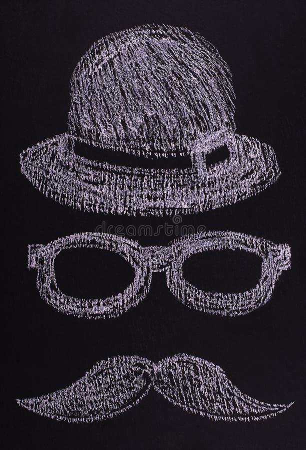 De hoed, de glazen en een snor in de vorm van een mens ` s zien getrokken krijt op een zwarte raad onder ogen Vlak leg stock afbeeldingen