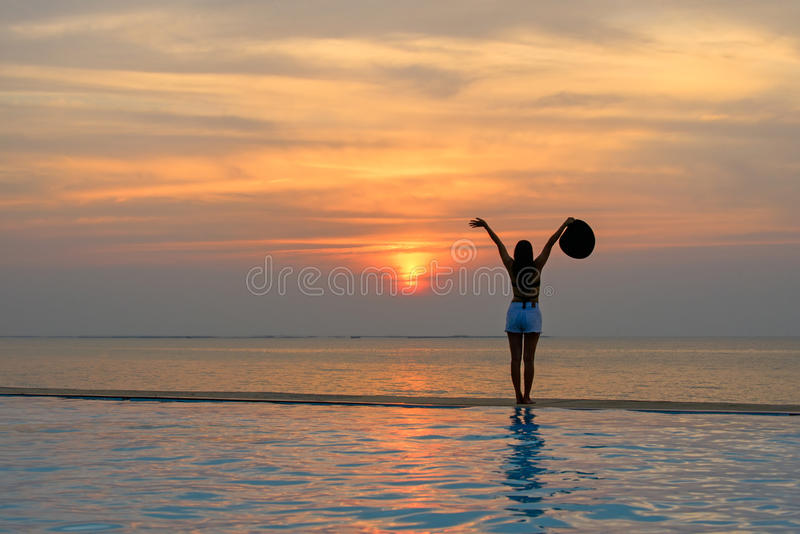 De hoed van de vrouwenholding het ontspannen bij de pool op de zonsondergang stock foto