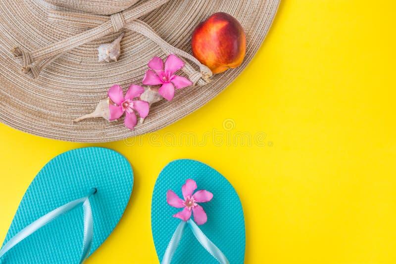 De hoed van het vrouwen` s stro, doorboort tropische bloemen, blauwe pantoffels, overzeese shells, nectarine op gele achtergrond, stock foto