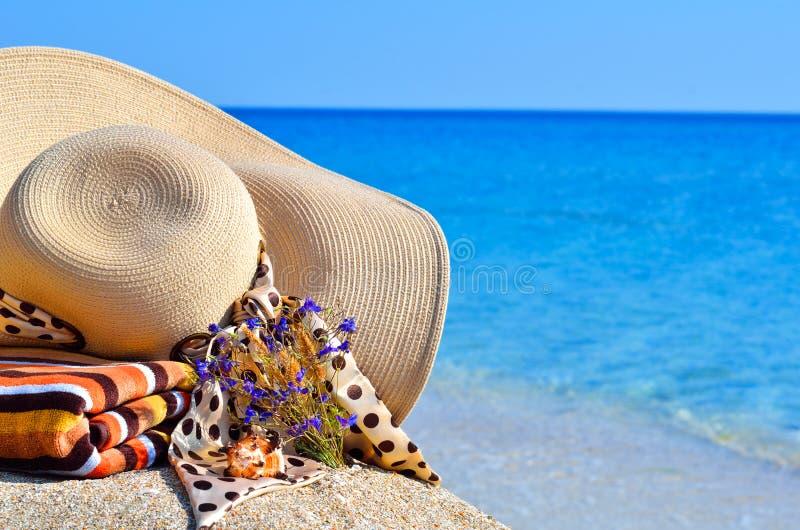 De hoed van het vrouwenstrand, heldere handdoek en bloemen tegen blauwe oceaan stock fotografie