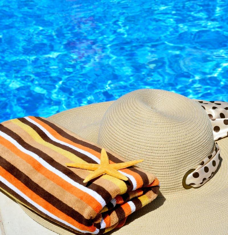 De hoed van het vrouwenstrand, heldere handdoek en zeester stock afbeelding