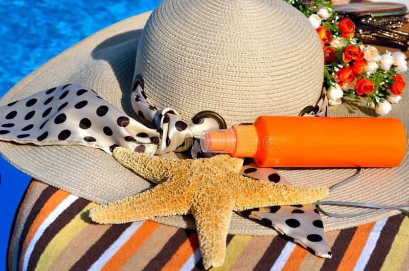 De hoed van het vrouwenstrand, heldere handdoek, hoofdtelefoons stock foto's