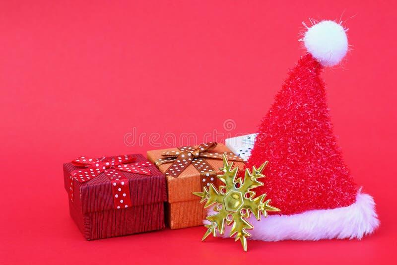 de hoed van de Kerstman met giftdozen en gouden sneeuwvlok op rood stock afbeeldingen