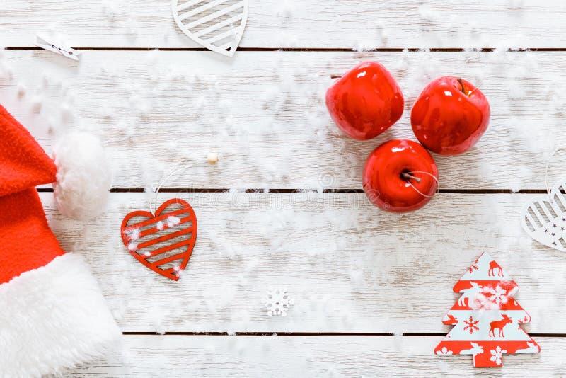 De hoed van de Kerstman, rode appelen op houten witte achtergrond, kopieert ruimte, hoogste mening, vrolijke Kerstmis, gelukkige  stock foto's