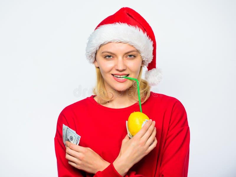 De hoed van meisjessanta drinkt bankbiljet van de sap het citroen verpakte dollar Bron van rijkdom Het concept van het rijkdomsym stock foto