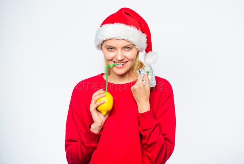 De hoed van meisjessanta drinkt het stro van de sapcitroen terwijl greepstapel van geld De wensen van Kerstmis Rijk meisje met ci stock afbeeldingen