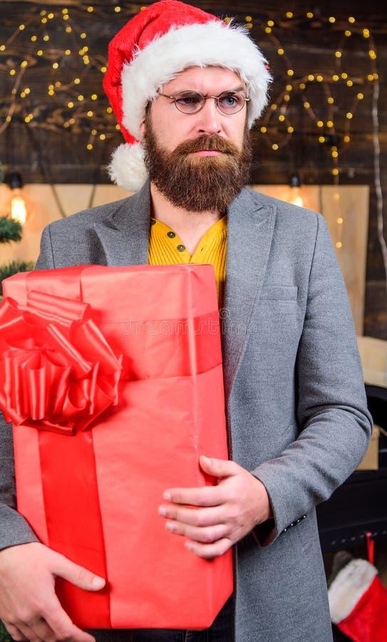 De hoed van mensensanta levert gift Uitgespreide geluk en vreugde Het gebaarde kerel ernstige gezicht draagt huidige doos leverin royalty-vrije stock afbeelding