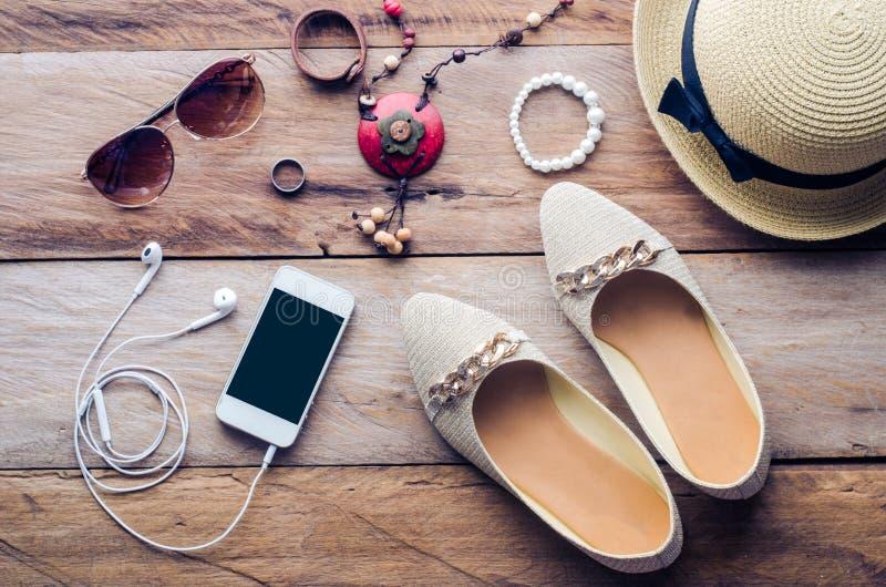 De hoeden, de schoenen en de toebehoren om zich te kleden leggen op de houten vloer voor reis - Uitstekende toon stock fotografie