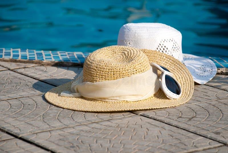 De hoeden van het stro en de Zonnebril liggen op de rand stock afbeeldingen
