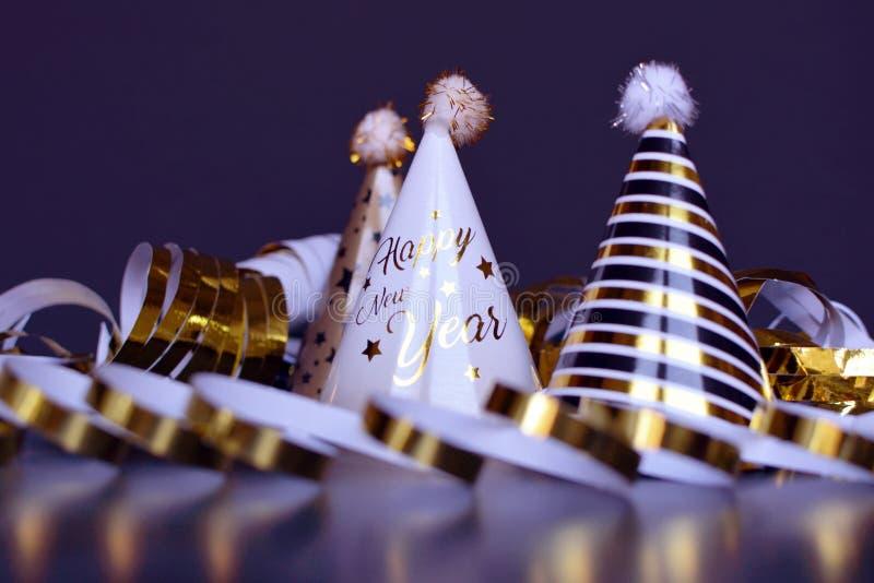De hoeden van de nieuwjaar silvester partij en gouden slingerwimpels op donkerblauwe achtergrond stock foto's